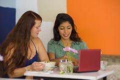 Jonge aantrekkelijke Latijnse meisjeszitting bij moderne koffie die lunch met gelukkige vrouw hebben als meisjes die voor binnen  stock fotografie