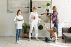 Jonge aantrekkelijke lesbische familie die in vrijetijdskleding tijd samen in de woonkamer doorbrengen royalty-vrije stock afbeelding