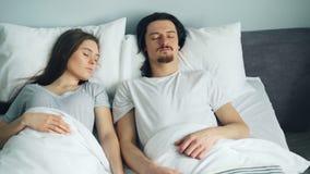 Jonge aantrekkelijke man en vrouwenslaap in bed die thuis samen rusten stock videobeelden