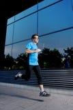 Jonge aantrekkelijke mens die en op stedelijke straatachtergrond lopen opleiden op de zomertraining in sportpraktijk Stock Fotografie