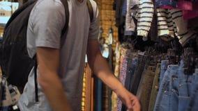 Jonge aantrekkelijke mens die jeans in winkel kiezen stock videobeelden