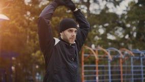 Jonge aantrekkelijke mens die jogger alvorens in openlucht in de winterpark te lopen opwarmen royalty-vrije stock foto