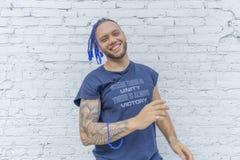 Jonge aantrekkelijke mens die met blauwe dreadlocks aan camera glimlachen royalty-vrije stock afbeeldingen