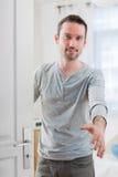 Jonge aantrekkelijke mens die u welkom heten in zijn huis Stock Fotografie
