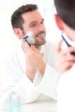 Jonge aantrekkelijke mens die zijn baard voor een spiegel scheren Stock Afbeelding