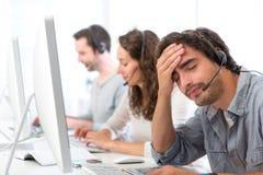 Jonge aantrekkelijke mens onbehaaglijk op het werk Stock Foto