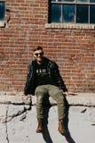 Jonge Aantrekkelijke Moderne Manier Kaukasisch Mannelijk Guy Walking die, Zitting, en buiten Stedelijke Oude Verlaten Baksteen Wa royalty-vrije stock fotografie