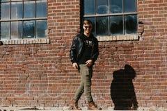 Jonge Aantrekkelijke Moderne Manier Kaukasisch Mannelijk Guy Walking die, Zitting, en buiten Stedelijke Oude Verlaten Baksteen Wa stock foto's