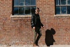 Jonge Aantrekkelijke Moderne Manier Kaukasisch Mannelijk Guy Walking die, Zitting, en buiten Stedelijke Oude Verlaten Baksteen Wa stock fotografie