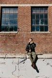 Jonge Aantrekkelijke Moderne Manier Kaukasisch Mannelijk Guy Walking die, Zitting, en buiten Stedelijke Oude Verlaten Baksteen Wa royalty-vrije stock afbeelding