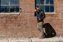 Jonge Aantrekkelijke Moderne Manier Kaukasisch Mannelijk Guy Walking die, Zitting, en buiten Stedelijke Oude Verlaten Baksteen Wa stock afbeeldingen