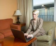 Jonge aantrekkelijke onderneemster die in een hotel werken Stock Foto's