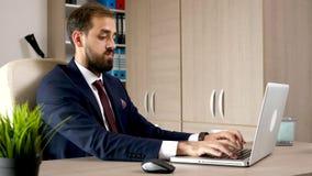 Jonge aantrekkelijke ondernemer in zijn bureau die aan de computer werken stock footage