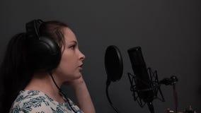 Jonge aantrekkelijke pop vrouwelijke ster in hoofdtelefoons die aan microfoon zingen Leuk meisje die lied in verslagstudio uitvoe stock videobeelden