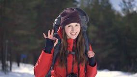 Jonge aantrekkelijke positieve wandelaar die en de camera glimlachen onderzoeken stock video