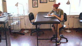 Jonge aantrekkelijke rode haired de kunstenaarszitting van de vrouwentatoegering bij lijst en het creëren van schets voor binnen  stock videobeelden