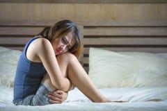 Jonge aantrekkelijke Spaanse vrouwenzitting op bed die maag aan gewrongen pijn en periodepijn lijden die ziek en onwel in cyclus  royalty-vrije stock foto