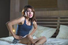 Jonge aantrekkelijke Spaanse vrouwenzitting op bed die maag aan gewrongen pijn en periodepijn lijden die ziek en onwel in cyclus  stock foto's