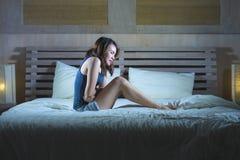 Jonge aantrekkelijke Spaanse vrouwenzitting op bed die maag aan gewrongen pijn en periodepijn lijden die ziek en onwel in cyclus  stock foto