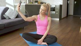 Jonge aantrekkelijke sportieve vrouwenzitting die op yogamat selfie met haar mobiele telefoon maken stock footage