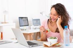 Jonge aantrekkelijke student die salade eten terwijl het telefoneren Stock Foto's