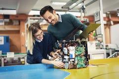 Jonge aantrekkelijke studenten die mechatronics aan project werken stock foto's