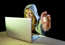 Jonge aantrekkelijke tienervrouw die hoodie het binnendringen in een beveiligd computersysteem laptop dragen cyberc Stock Foto's