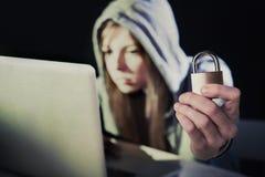 Jonge aantrekkelijke tienervrouw die hoodie het binnendringen in een beveiligd computersysteem laptop dragen cyberc Stock Afbeelding