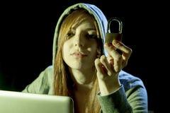 Jonge aantrekkelijke tienervrouw die kap op het binnendringen in een beveiligd computersysteem laptop het concept van de computer Stock Afbeelding