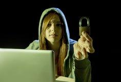 Jonge aantrekkelijke tienervrouw die kap op het binnendringen in een beveiligd computersysteem laptop het concept van de computer Stock Afbeeldingen
