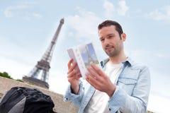 Jonge aantrekkelijke toerist die een gids van Parijs lezen royalty-vrije stock afbeelding