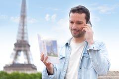 Jonge aantrekkelijke toerist die een gids van Parijs lezen stock afbeeldingen