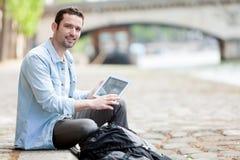 Jonge aantrekkelijke toerist die tablet in Parijs gebruiken royalty-vrije stock foto