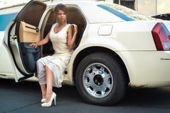 Jonge aantrekkelijke VIP Vrouw die van limousine met deur weggaan die open zijn royalty-vrije stock afbeelding