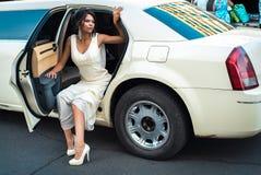 Jonge aantrekkelijke VIP Vrouw die van limousine met deur weggaan die open zijn royalty-vrije stock afbeeldingen