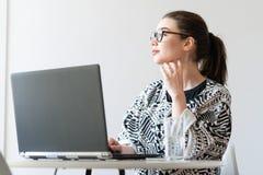 Jonge aantrekkelijke vrouw die aan laptop in moderne heldere flats werken stock afbeelding