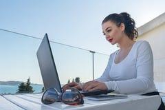 Jonge aantrekkelijke vrouw die aan laptop op balkon werken en van mooi Weergeven genieten royalty-vrije stock foto