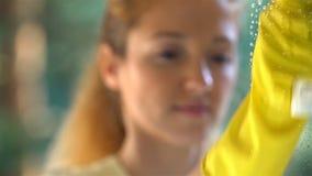 Jonge aantrekkelijke vrouw die een venster schoonmaken Dolly schot stock videobeelden