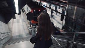 Jonge aantrekkelijke vrouw die elegant onderaan de metroroltrap gaan stock video