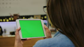 Jonge aantrekkelijke vrouw die in glazen op video op tablet met het groene scherm in de koffie letten Close-up Twee in: 1 stock videobeelden