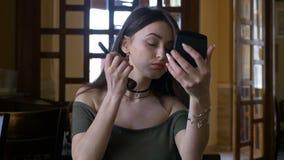 Jonge aantrekkelijke vrouw die haar make-up retoucheren bij een restaurant vóór vergadering stock footage