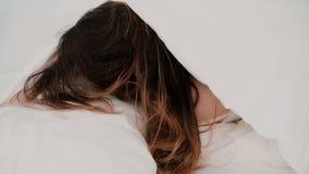 Jonge aantrekkelijke vrouw die in het bed liggen, die van de ochtend thuis genieten Meisje die de camera en het glimlachen bekijk stock video