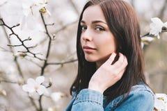 Jonge aantrekkelijke vrouw die het blauwe modieuze jeansjasje stellen dragen Stock Foto