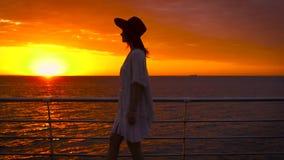 Jonge aantrekkelijke vrouw die het witte kleding en hoeden stellen op overzeese achtergrond dragen bij verbazende zonsondergang stock videobeelden