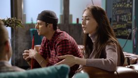 Jonge aantrekkelijke vrouw die iets vertelt aan vrienden die in een koffie zitten stock videobeelden