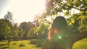 Jonge aantrekkelijke vrouw die met geluk in park lopen stock videobeelden