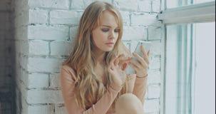 Jonge aantrekkelijke vrouw die mobiele telefoon met behulp van terwijl thuis het zitten dichtbij het venster stock footage