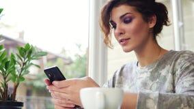 Jonge aantrekkelijke vrouw die online gebruikend haar mobiele telefoon in koffie en het glimlachen winkelen Vrouw die app op smar stock videobeelden