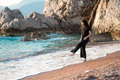 Jonge aantrekkelijke vrouw die op een zonnig strand bij kust lopen Reiziger en blogger royalty-vrije stock foto's