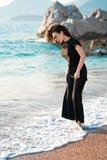 Jonge aantrekkelijke vrouw die op een zonnig strand bij kust lopen Reiziger en blogger stock afbeelding
